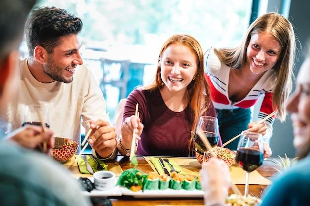 Amigos felizes comendo com pauzinhos em restaurante de sushi