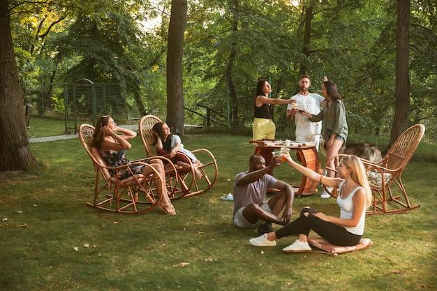 Amigos felizes comendo e bebendo cerveja em um jantar de churrasco na hora do pôr do sol