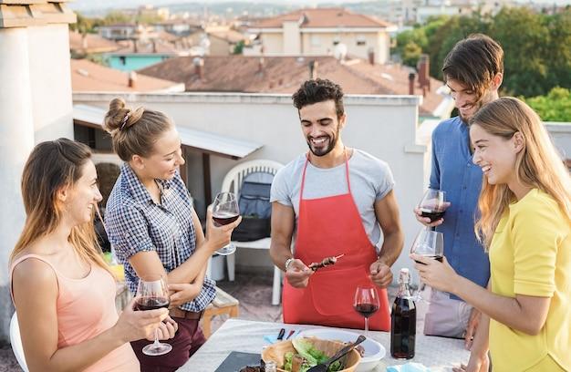 Amigos felizes comendo e bebendo vinho juntos em uma festa de churrasco ao ar livre - foco principal no rosto da garota certa