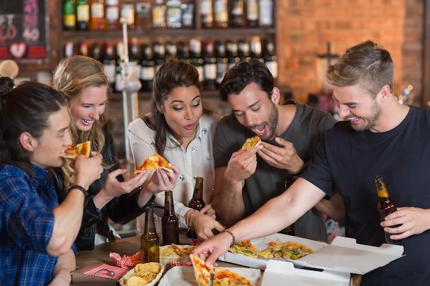 Amigos felizes comendo pizza com cerveja