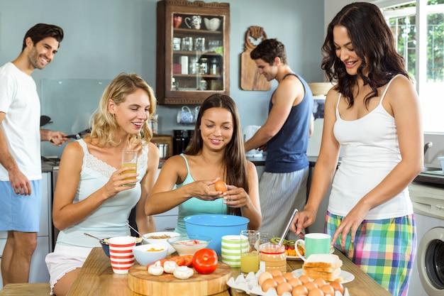Amigos felizes cozinhando comida juntos na cozinha