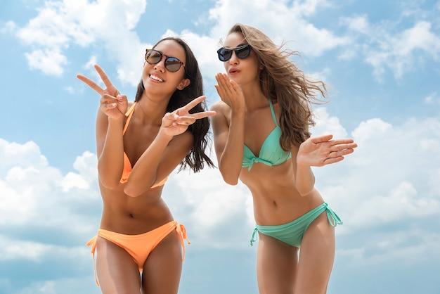Amigos felizes da mulher bonita em biquínis coloridos na praia no verão