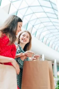 Amigos felizes de baixo ângulo no shopping