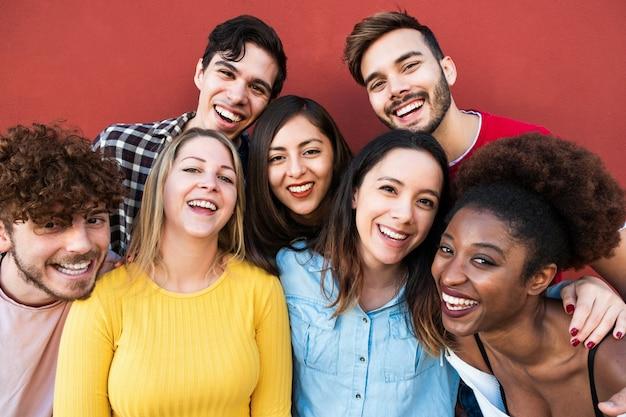 Amigos felizes de diferentes raças e culturas rindo na frente da câmera do telefone - jovens milenares se divertindo juntos - conceito de geração multirracial - foco principal no rosto de menina loira
