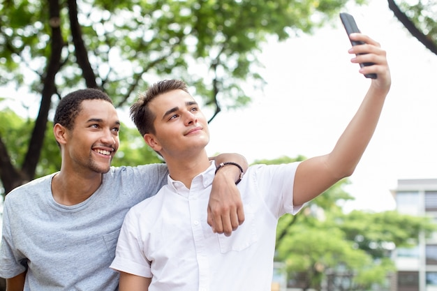 Amigos felizes de jovens estudantes do sexo masculino levando selfie