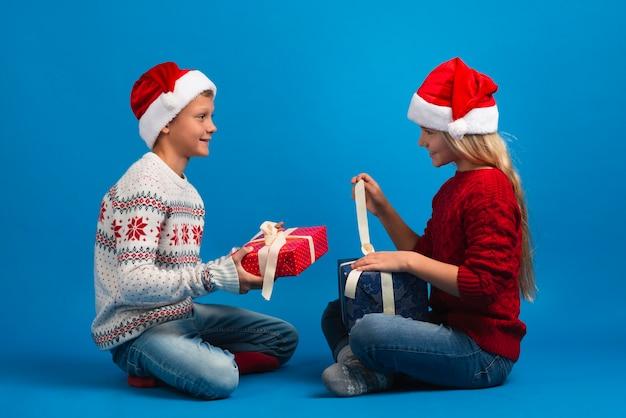 Amigos felizes, desembrulhando presentes de natal