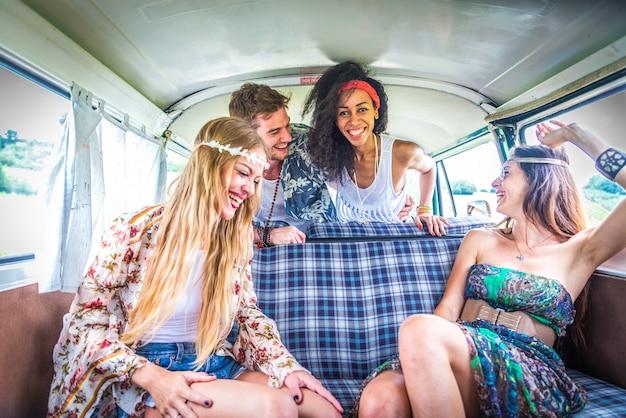 Amigos felizes dirigindo uma minivan vintage