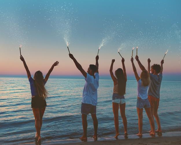 Amigos felizes e sorridentes na praia com velas cintilantes na mão