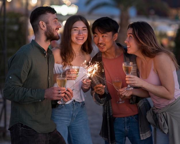 Amigos felizes em festa com fogos de artifício