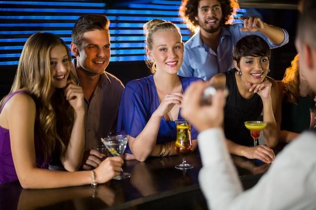 Amigos felizes em pé no balcão de bar
