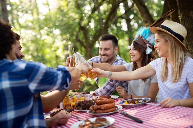 Amigos felizes fazendo churrasco e almoçando na natureza