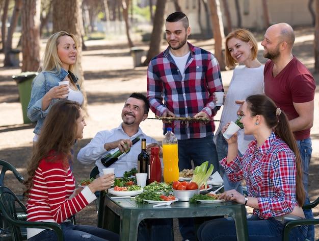 Amigos felizes fazendo churrasqueira