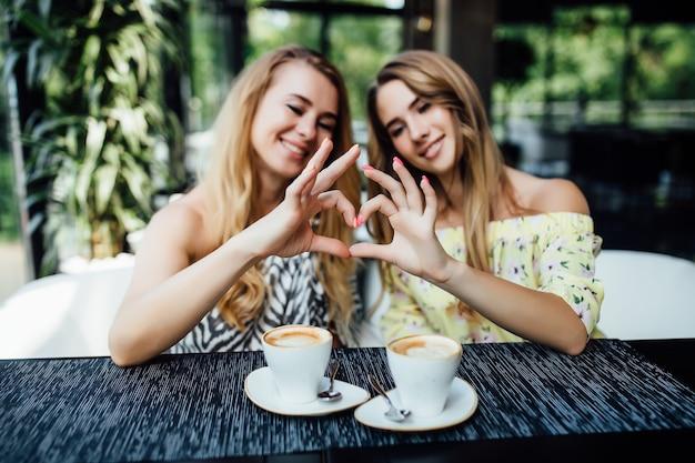 Amigos felizes fazendo gestos de coração e tomando café no terraço