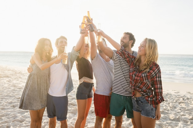 Amigos felizes levantando garrafas de cerveja