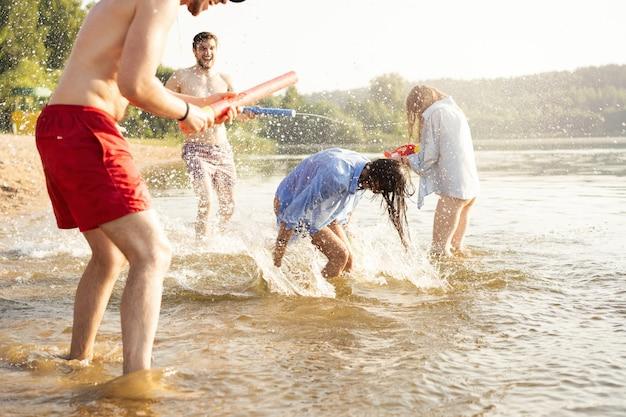 Amigos felizes lutando com armas de água - juventude, estilo de vida de verão e conceito de férias