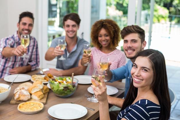 Amigos felizes, mostrando o vinho durante a refeição