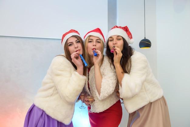 Amigos felizes na festa de ano novo comemorando. três mulheres em elegantes vestidos de noite e jaquetas de pele