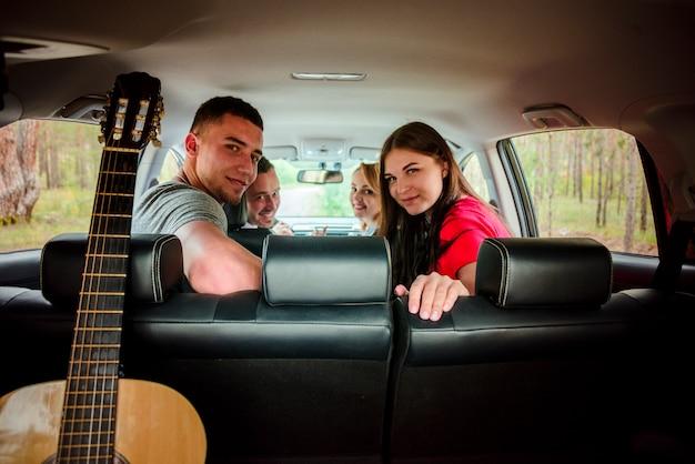 Amigos felizes na vista traseira do carro