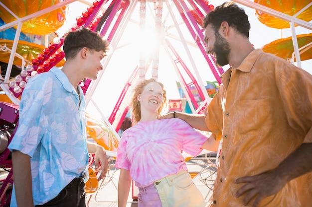 Amigos felizes no parque de diversões na luz solar