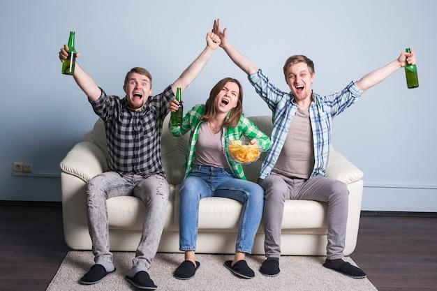 Amigos felizes ou fãs de futebol assistindo futebol na tv e comemorando a vitória em casa. conceito de amizade, esportes e entretenimento.