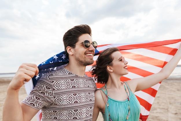 Amigos felizes passando um tempo na praia segurando bandeira americana