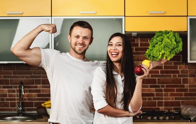 Amigos felizes preparando comida para o jantar, posando na cozinha segurando frutas e legumes. homem mostra bíceps no braço. promovendo uma alimentação saudável