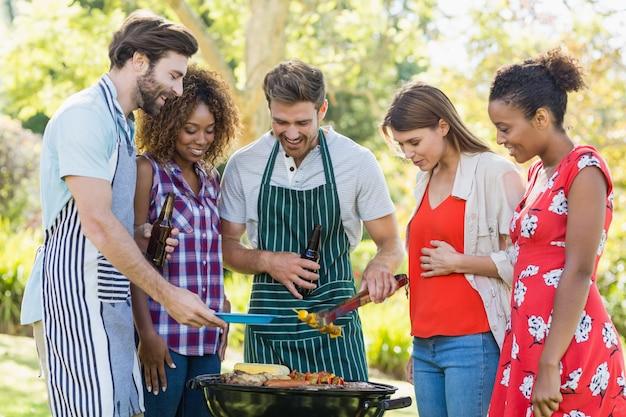 Amigos felizes, preparando uma churrasqueira no parque