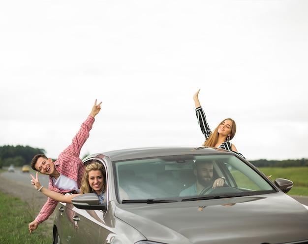Amigos felizes que apreciam a viagem de carro