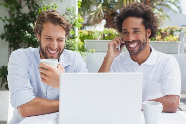 Amigos felizes que apreciam o café junto com o portátil