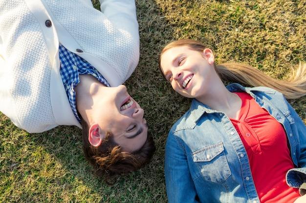 Amigos felizes que encontram-se na grama e que riem