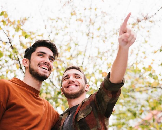 Amigos felizes que olham na distância