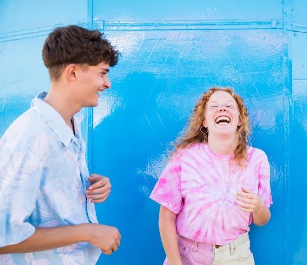 Amigos felizes rindo com parede azul atrás