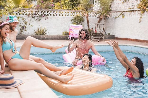 Amigos felizes, salpicos de água na festa na piscina - jovens se divertindo nas férias de verão