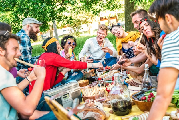 Amigos felizes se divertindo ao ar livre, comer lanche e beber vinho tinto no piquenique de churrasco