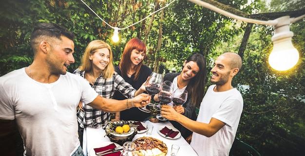 Amigos felizes, se divertindo, bebendo vinho tinto na festa no jardim do quintal