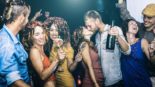 Amigos felizes se divertindo multirracial na celebração do ano novo - jovens bebendo e dançando na pós-festa na boate - conceito de amizade no humor bêbado - foco na mulher de pano amarelo