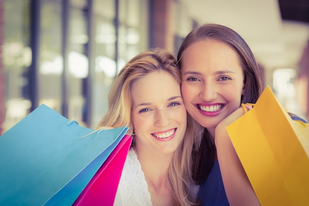 Amigos felizes segurando sacolas de compras