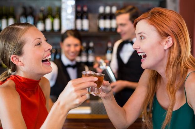 Amigos felizes, segurando um tiro de tequila na frente do balcão de bar