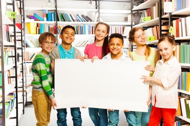 Amigos felizes segurando uma folha de papel branco na biblioteca