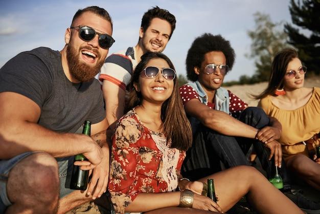 Amigos felizes sentados com garrafas de cerveja na praia ao pôr do sol