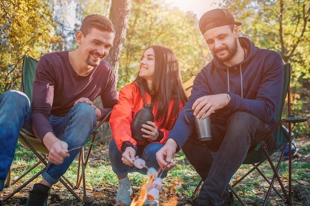 Amigos felizes sentados juntos e cozinhar murshmellow em chamas. ela olha para o cara da esquerda e ri. os jovens olham para o fogo. alguns deles têm garrafas térmicas nas mãos.