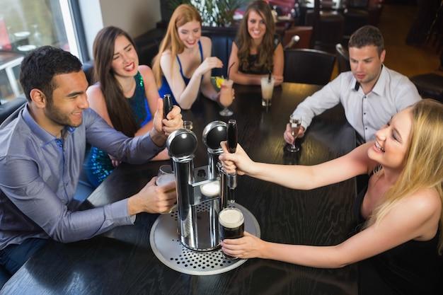 Amigos felizes sentados juntos e puxando pintas