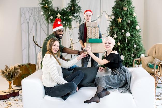 Amigos felizes sentados no sofá em casa bebendo champanhe e curtindo as férias de natal
