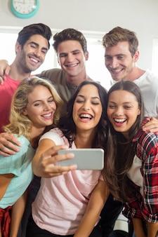 Amigos felizes sorrindo enquanto estiver a tomar selfie em casa