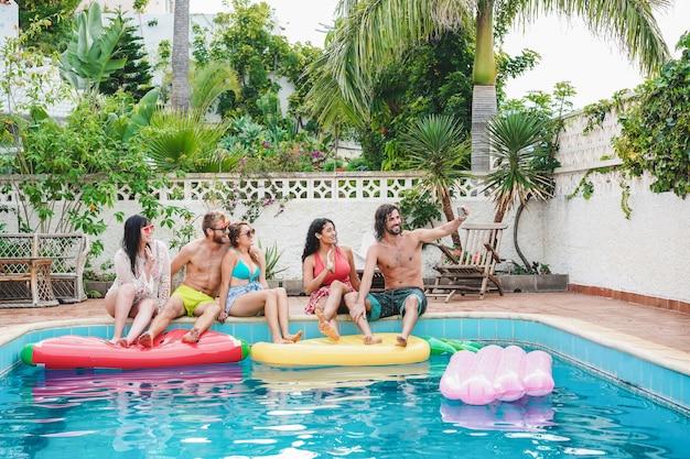 Amigos felizes tirando foto de selfie na festa na piscina - jovens se divertindo nas férias de verão