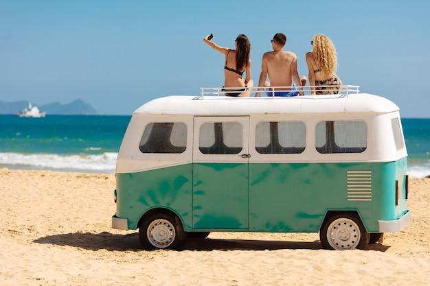 Amigos felizes tirando foto enquanto relaxa em cima do mini ônibus