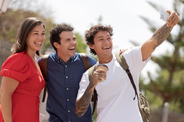 Amigos felizes tirando selfie em foto média