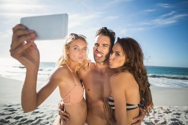 Amigos felizes tirando selfie na praia