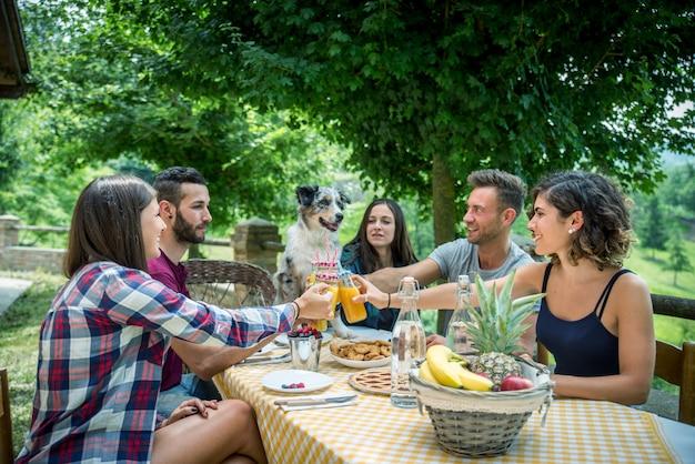 Amigos felizes tomando café da manhã em uma casa de campo