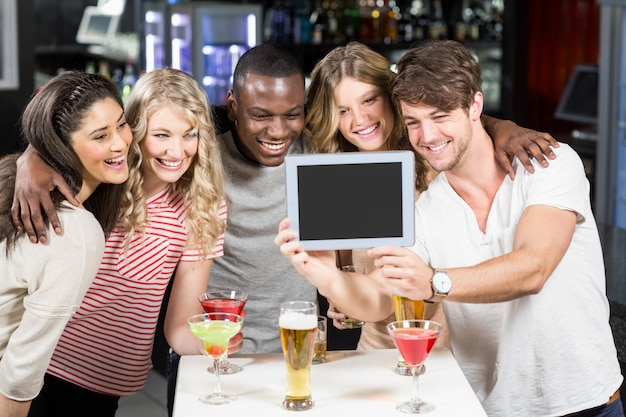 Amigos felizes tomando selfie com tablet